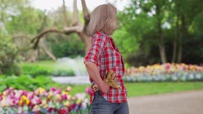 Senior Caucasian woman standing in community flower garden with work gloves