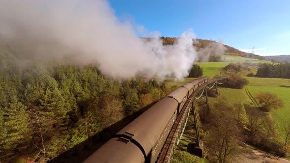 Thumbnail for Nostalgic Steam Engine Train on Railroad Bridge