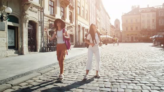 Cover Image for Lady Tourists with Backpacks Walking in City