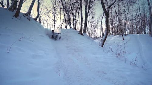 Happy Man Rides a Sled From a Snow Hill