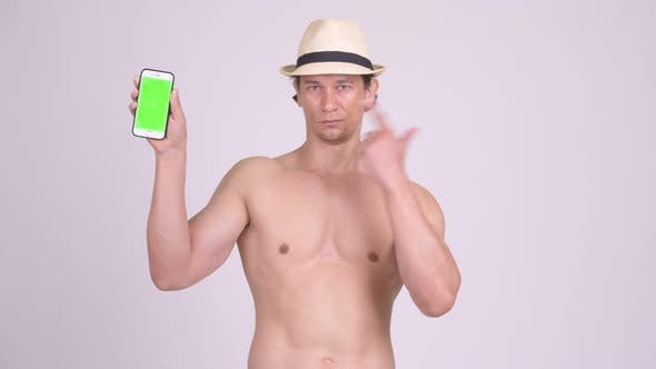 Thumbnail for Happy Muscular Tourist Man Showing Phone and Giving Thumbs Up Shirtless