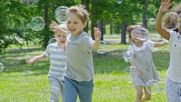 Thumbnail for Laughing Boys and Girls Popping Bubbles in the Park