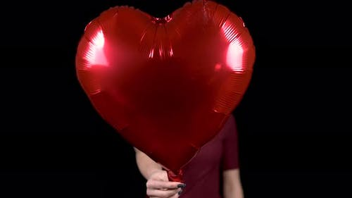 A Young Woman Holds Out a Heart-shaped Balloon Towards the Camera. A Woman Is Standing with a Helium