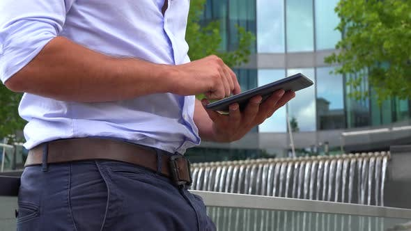 Thumbnail for A Businessman Works on a Tablet - Closeup - an Office Building in the Blurry Background