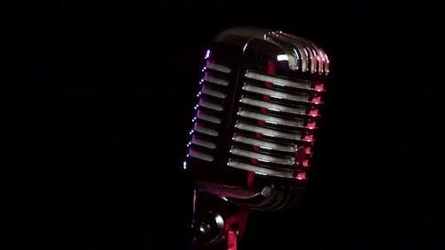 Klassisches Vokalmikrofon dreht und reflektiert Bühnenlichter
