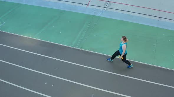 Thumbnail for Aerial View of Woman Doing Lunges on Stadium Track