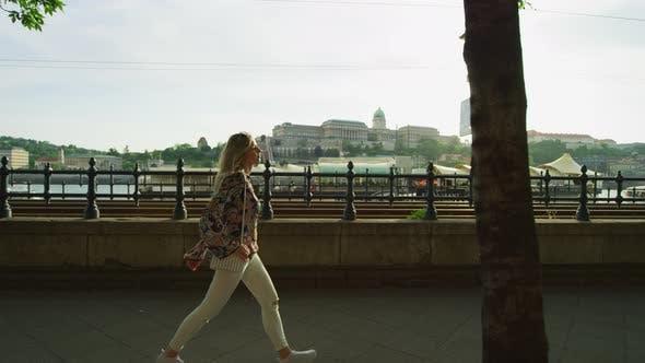 Thumbnail for Woman walking along the riverside