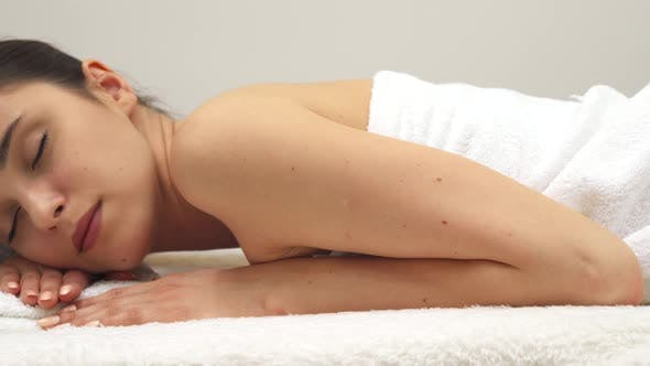 Thumbnail for Girl Lies on Her Stomach on the Massage Table