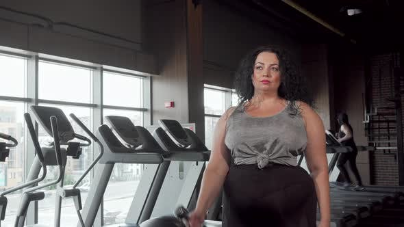 Thumbnail for Beautiful Overweight Woman Exercising with Dumbbells at the Gym