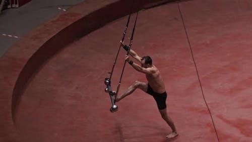 Ein akrobatischer Mann, der eine Show auf dem fliegenden Bau macht und den Bau schwingt
