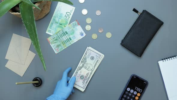 Hands in protective gloves putting money on desk
