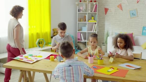 Thumbnail for Little Children Making Origami Boats with Help of Kindergarten Teacher