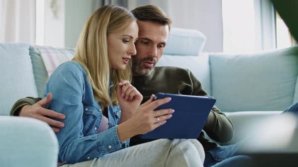 Thumbnail for Loving couple using a tablet in living room