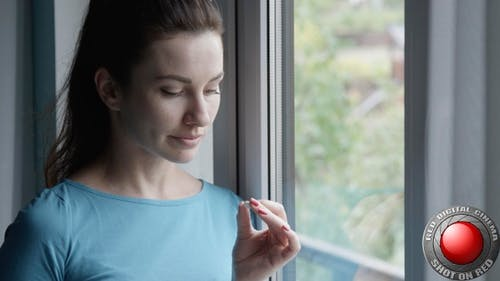 Woman Taking A Pill And Drinking A Glass Of Water Standing By The Window