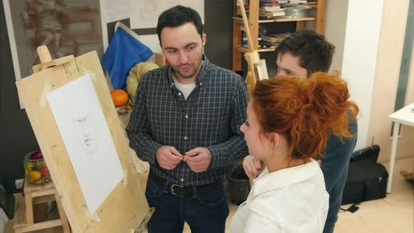 Thumbnail for Three Art Students Standing Next To the Easel and Having a Discussion