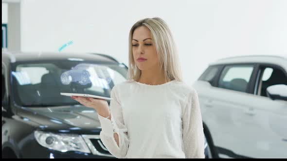Thumbnail for A Girl Is Holding a Tablet on Which a Car Hologram Is Projected