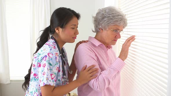 Thumbnail for Mature Caucasian woman being consoled by Japanese nurse