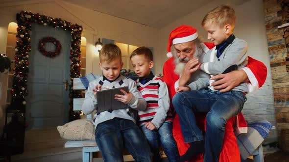Thumbnail for Little Boys  with Santa Claus Playing with Tablet.