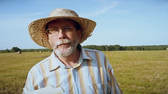 Thumbnail for Senior man eats melon in the meadow