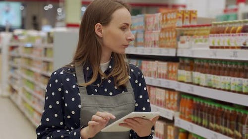 Woman in an Apron Working in a Supermarket