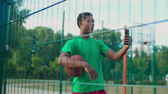 Streetball Player with Phone Live Streaming on Court