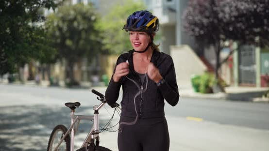 Thumbnail for Woman in sportswear using device post workout with bike on street in daytime