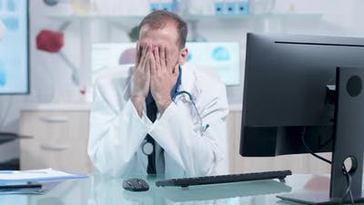Tired Doctor in His Office is Working
