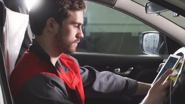 Thumbnail for Der Reparaturmann, der in einer Arbeitsuniform gekleidet ist, ist im Fahrzeug und überprüft das Getriebe