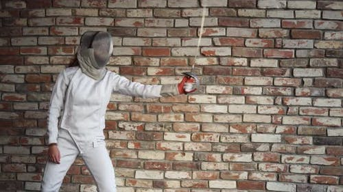 A Woman in a Protective Helmet Demonstrates Her Ability To Professionally Fence
