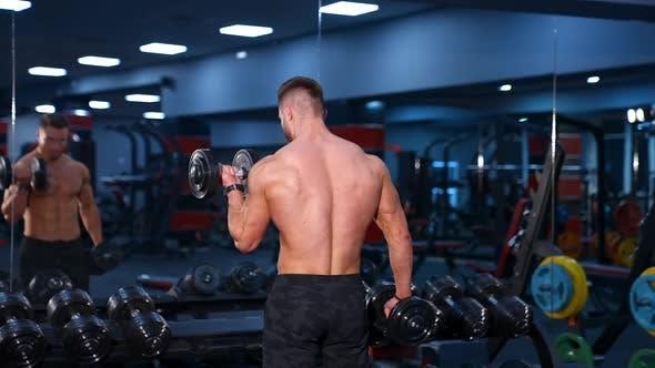 Starker junger Mann mit athletischem Körper macht Übungen mit Hanteln