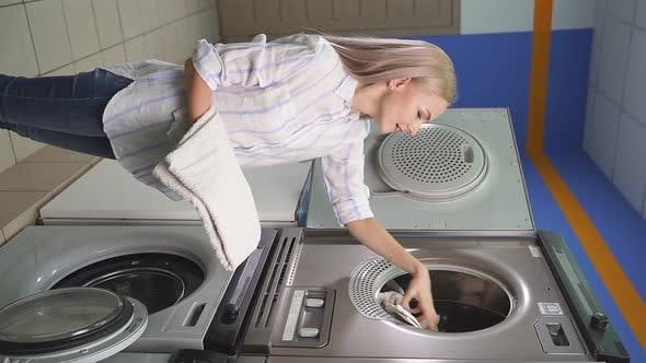 Woman in a Public Laundry Loading Laundry a Public Selfservice Place