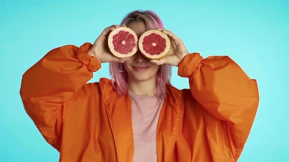 Cover Image for Joyful young hipster with dyed pink hairstyle with two half of juicy grapefruit on eyes