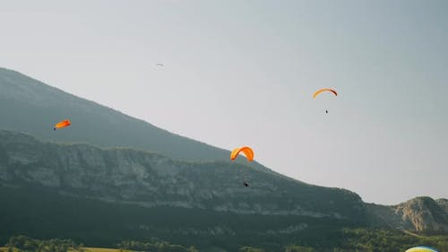Orange paraplanes flying above Alps mountains