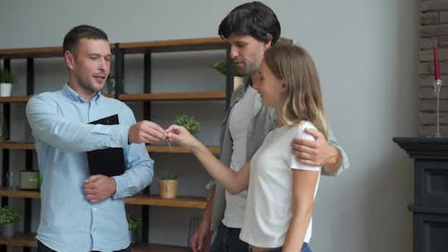 Happy Couple Receiving Apartment Key From Real Estate Agent. Happy Couple Smiling and Getting Keys