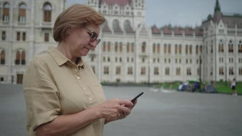 Mature Woman with Cell at Kossuth Square in Budapest Hungary