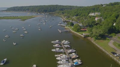 Aerial View of a Small Marina and Boats Anchored on Harbor Near a Small Town