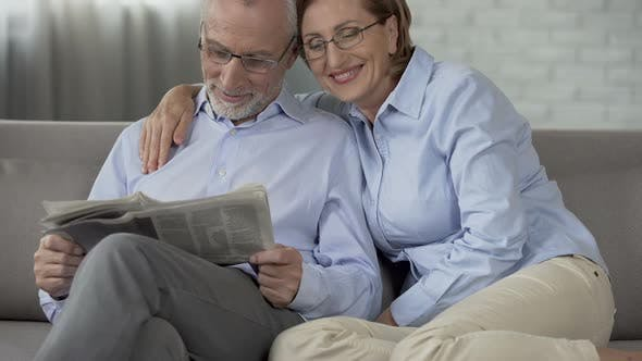 Thumbnail for Old Man Reading Newspaper, Woman Putting Arm Around His Shoulders, Gentleness