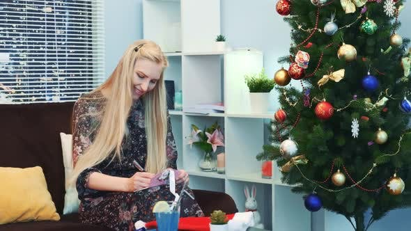 Thumbnail for Smiling Young Woman Writing Letter Near the Xmas Tree on the New Year's Eve