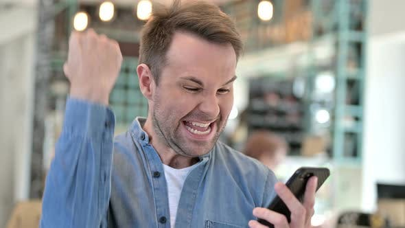 Thumbnail for Portrait of Casual Man Celebrating Success on Smartphone