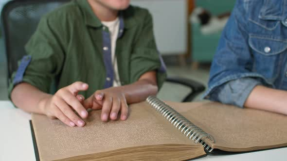 Disability Closeup of Blind Boy Moving His Fingers While Reading Braille Book Kid Studying at Home