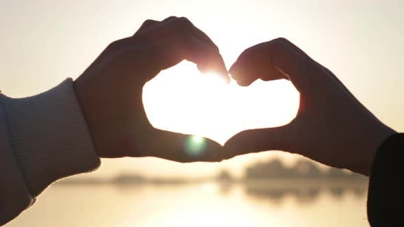 Thumbnail for Hands of Men and Women Came Together and Show Form the Symbol of a Heart Shape at Sunset