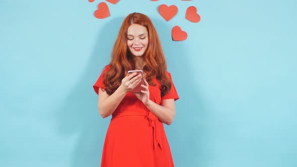 Portrait of Young Surprised Woman with Red Hair Looking at Screen of Mobile Phone in Shock.