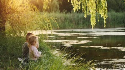 Couple of Children Sitting By the Lake at Sunset