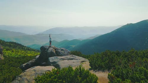 Happy Woman Hiker in the Mountains Rotating Standing on a Rock with Arms Raised