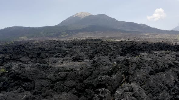 Thumbnail for Flying low level over solid, black lava towards a volcano