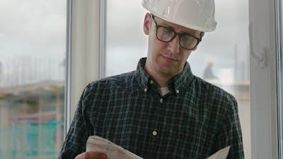 Builder engineer wear security helmet look at blueprint