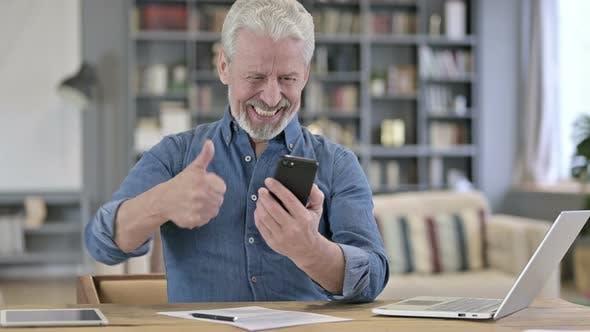 Old Man Celebrating Success on Smartphone