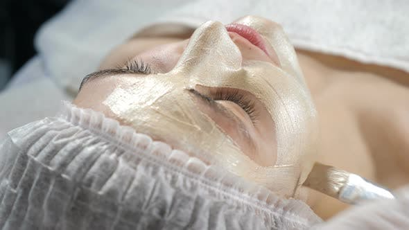 Top View on Young Attractive Female Client Getting Beauty Facial Procedure in Beauty Clinic. Lifting