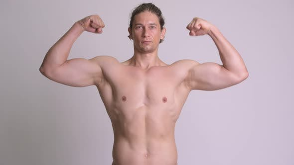 Thumbnail for Handsome Muscular Man Flexing Biceps Shirtless Against White Background