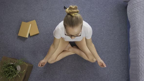 Thumbnail for Teenage Girl Meditating on Floor at Home